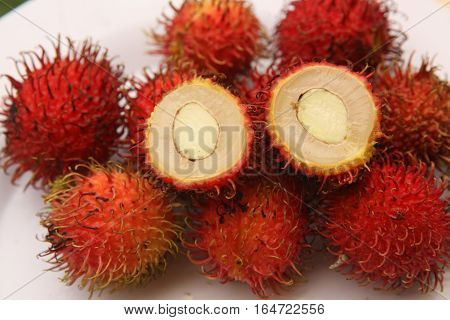 rambutan berries fruit close up photo on plate
