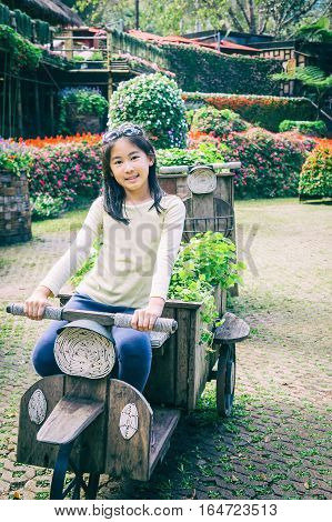 outdoor portrait of girl riding wooden motobike in park vintage style