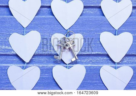 Paper hearts and silver keys on purple wooden background. Horizontal orientation Close- up. Valentine background.