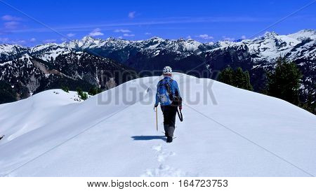 Woman walking on mountain top with snow. Ruth Mountain North Cascades National Park Seattle Washington State USA