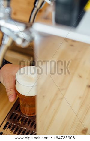 Unrecognizable man holding glass of light craft beer with froth.From above