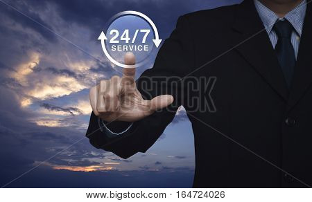 Businessman pressing button 24 hours service icon over sunset sky with clouds Full time service concept