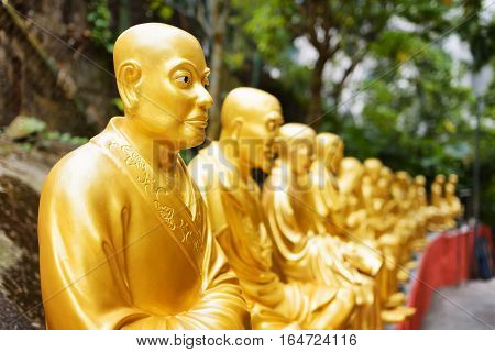 Golden Buddha Statues And Landscape With Green Trees