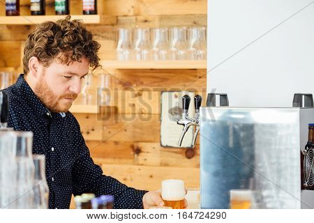 Curly-haired man holding glass of craft beer covered with froth