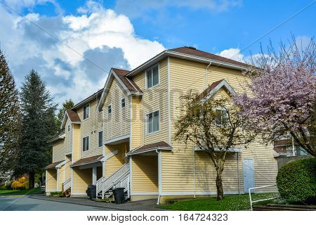 Residential complex of townhouses on cloudy sky background. Spring season in Vancouver