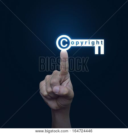 Hand pressing copyright key icon on blue background Copyright and patents concept
