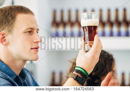 Side view of blond man looking at dark craft beer