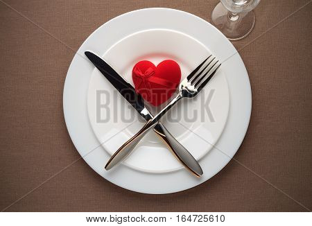 Valentines Day Table Setting With Red Heart, White Plates, Fork, Knife And Wineglass.