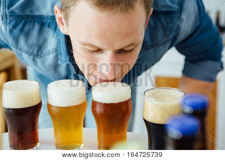 Close-up of blond man smelling different craft beer with froth