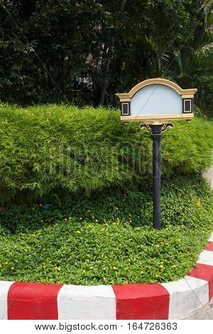 Decorative empty sign on a green lawn in a driveway place for text. Ornate blank signboard with copy space by the entrance outdoors