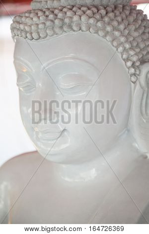 White peaceful Buddha statue meditating with closed eyes close-up. Religious stone sculpture at Buddhist shrine in Thailand