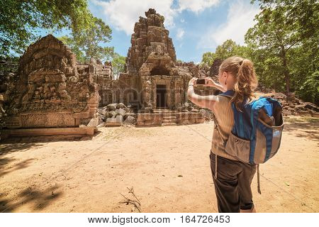 Tourist Photographing Gopura And Bas-relief In Angkor, Cambodia