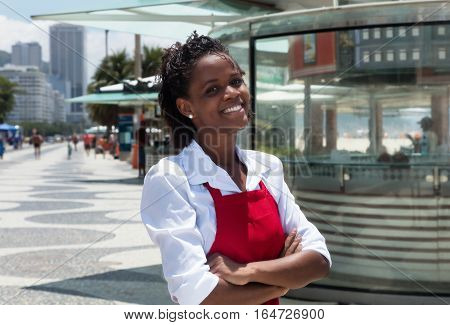 Laughing african american waitress in front of the restaurant outdoor in the summer