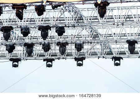 Illuminated multi-colored lights LED lights equipment attached to constuction steel frame. on outdoor concert stage