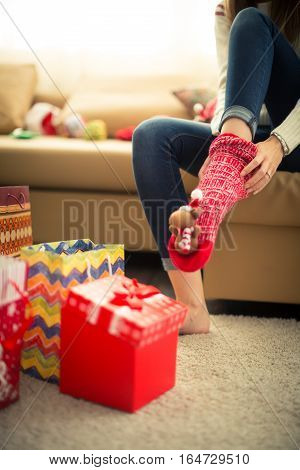 Close up of unrecognizable woman puts on red christmas socks