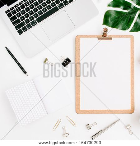 Home office workspace mockup with laptop clipboard palm leaf notebook and accessories. Flat lay top view