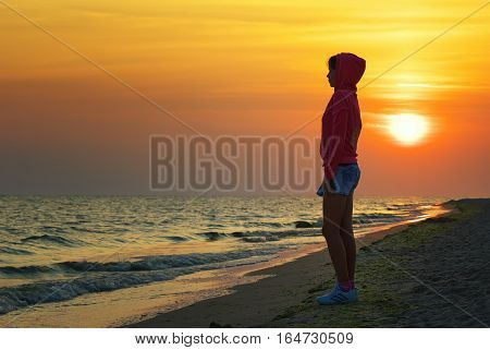 silhouette of the girl in sportswear with a hood at sunset