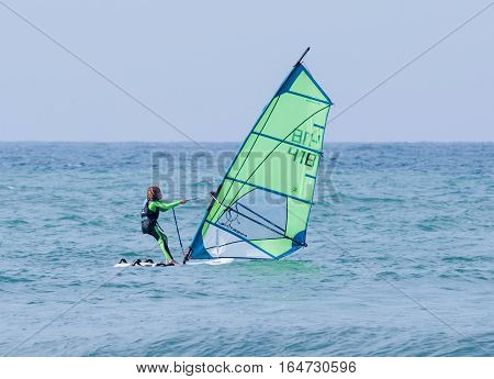 Girl Exercising In Windsurfing In The Mediterranean Sea