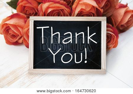 orange roses and blackboard with the words Thank You on wooden table