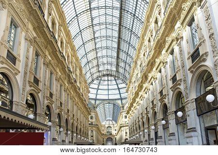 Italy Milan. Vittorio's galleries of Emmanuel II. The building of a passage with a glass roof has a form of a Latin cross with the octagonal center decorated with mosaics. The Milan trade gallery connects the square in front of a city cathedral to the squ