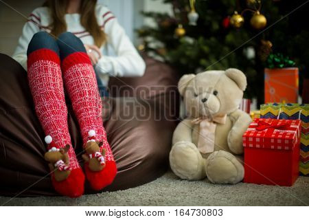 Close up of female legs in red christmas socks with fun fluffy elks. Christmas gifts and teddy bear under decorated pine tree.