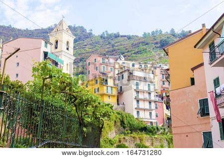 Manarola town Riomaggiore La Spezia province Liguria northern Italy. View of the colourful houses on surrounding hills and San Lorenzo defence bell tower. Part of the Cinque Terre National Park and a UNESCO World Heritage Site.