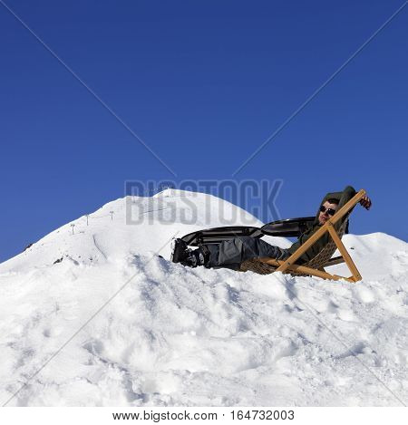 Skier At Winter Mountains Resting On Sun-lounger In Outdoor Cafe