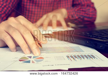 Data Analyzing With Businessman Holding Pen At Charts And Graph To Find Out The Result.