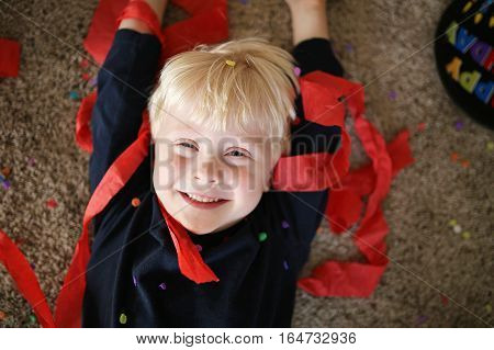 A happy little 4 year old boy is laying on the carpet with streamers and confetti smiling during a birthday party.
