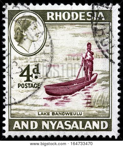 LUGA RUSSIA - SEPTEMBER 18 2015: A stamp printed by RHODESIA AND NYASALAND shows image portrait of Queen Elizabeth II against view of Bangweulu Lake 1959