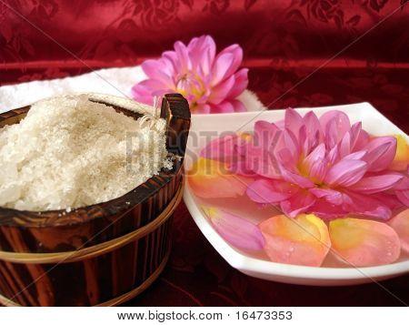 washtub with bath salt, towel and flowers