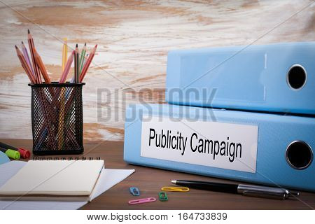 Publicity Campaign, Office Binder on Wooden Desk. On the table colored pencils, pen, notebook paper.