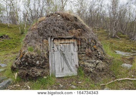 Sami culture: a turf goat hut (gaicagoahti) in a Sami Camp in Abisko National Park