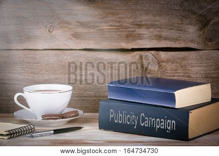 Publicity Campaign. Stack of books on wooden desk.