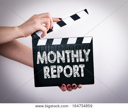 Monthly Report. Female hands holding movie clapper.