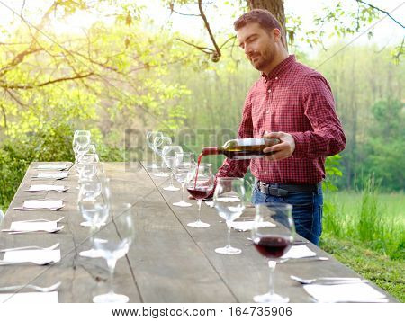 Portrait of wine producer pouring red wine into wine glasses