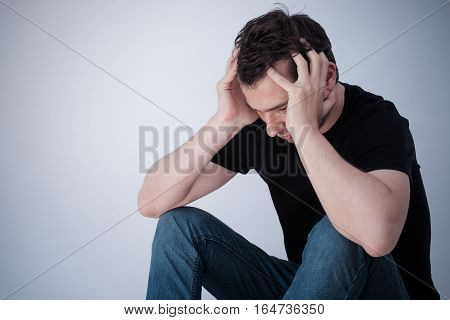 Portrait of thoughtful sad man alone on grey background