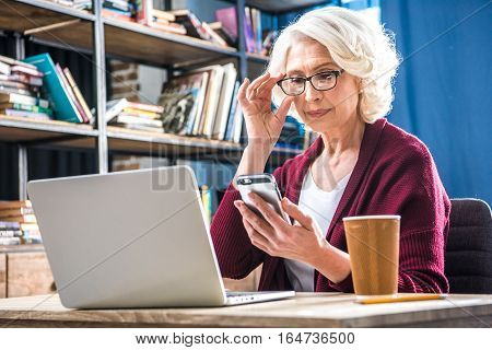 Attractive senior woman in eyeglasses using smartphone while sitting at desk with laptop and paper cup