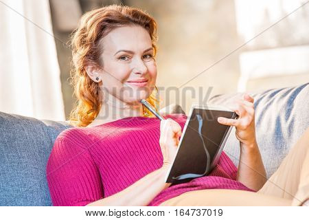 Portrait of smiling woman making notes in notepad