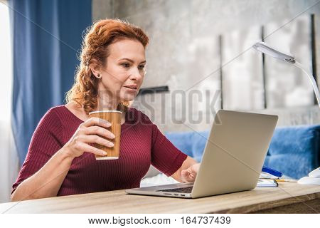 Attractive woman using laptop and holding paper cup