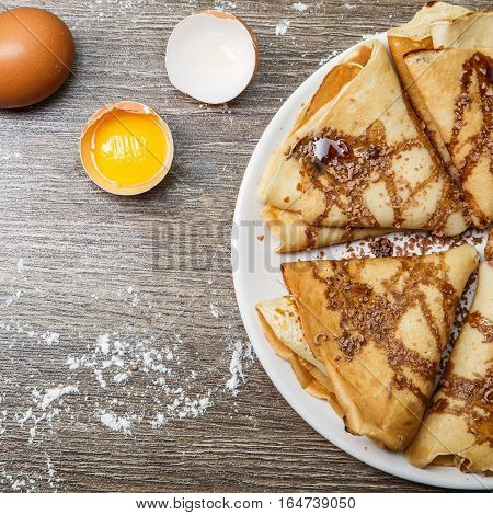Hotcakes with chocolate on plate on wooden table