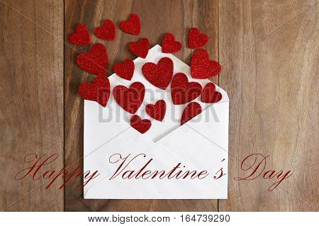 Valentine's Day Love Letter Spilling Out Red Hearts Onto Wood Background