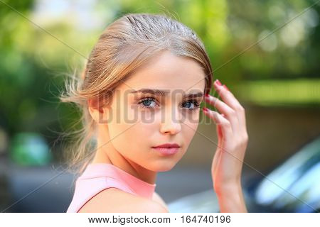 Pretty young woman or girl with tied in bun blonde hair in pink shirt with raised hand cute face on sunny day