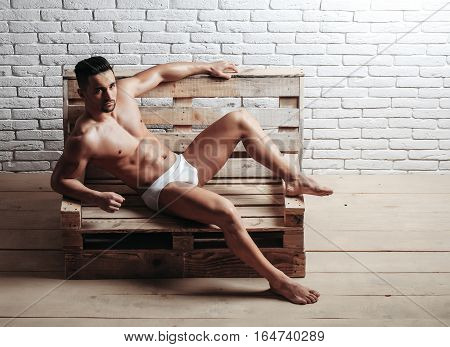 Handsome man or muscular macho bodybuilder with sexy muscle torso body with six packs and abs in sexi underpants on wooden pallet sofa on white brick wall background