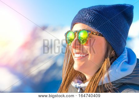 Female skier with skis smiling and wearing ski glasses. With reflection panorama of mountains