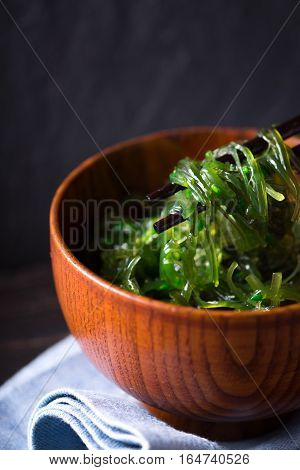 Wooden bowl with chuka salad on the dark background
