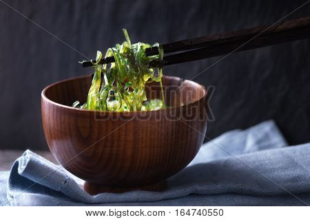 Chinese chopsticks with chuka salad horizontal background