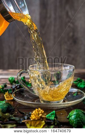 Tea poured into cup from glass carafe on decoration background of dried flower