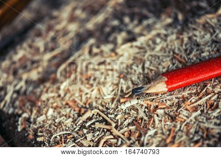 Red pencil on carpenters workshop table covered with wooden sawdust and scobs macro with selective focus