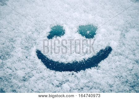 Happy smiley emoticon face in snow winter season joy and happiness concept